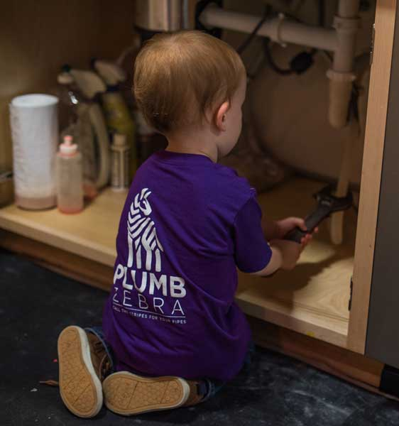 Image of owner's kid in plumb zebra t-shirt fixing drain under sink.